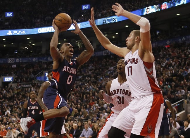 Mar 23, 2014; Toronto, Ontario, CAN; Atlanta Hawks guard Jeff Teague (0) goes up to make a shot as Toronto Raptors center Jonas Valanciunas (17) defends during the second half at the Air Canada Centre. Toronto defeated Atlanta 96-86. Mandatory Credit: John E. Sokolowski-USA TODAY Sports