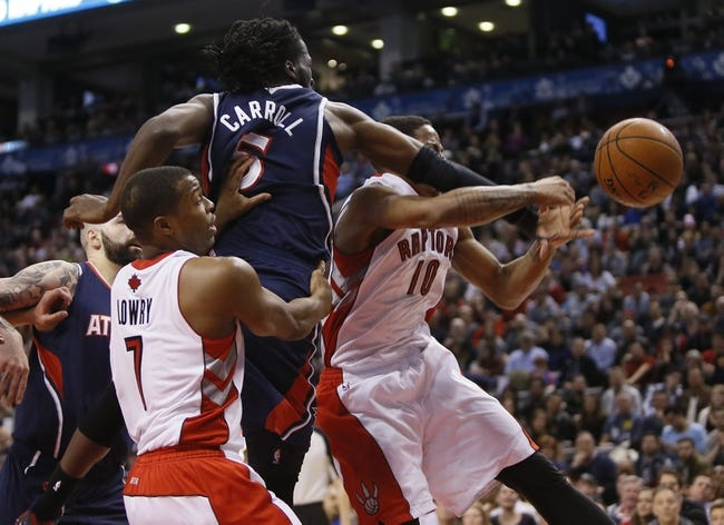 Mar 23, 2014; Toronto, Ontario, CAN; Atlanta Hawks forward DeMarre Carroll (5) fouls on Toronto Raptors guard DeMar DeRozan (10) as guard Kyle Lowry (7) helps out during the second half at the Air Canada Centre. Toronto defeated Atlanta 96-86. Mandatory Credit: John E. Sokolowski-USA TODAY Sports