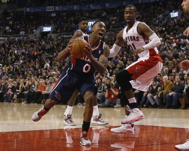 Mar 23, 2014; Toronto, Ontario, CAN; Atlanta Hawks guard Jeff Teague (0) goes to make a shot as Toronto Raptors guard Terrence Ross (31) looks on during the second half at the Air Canada Centre. Toronto defeated Atlanta 96-86. Mandatory Credit: John E. Sokolowski-USA TODAY Sports
