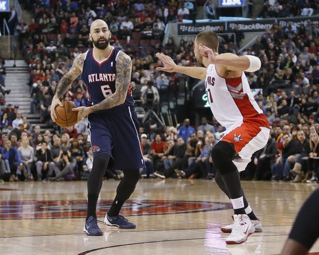 Mar 23, 2014; Toronto, Ontario, CAN; Atlanta Hawks center Pero Antic (6) looks to pass as Toronto Raptors center Jonas Valanciunas (17) defends during the second half at the Air Canada Centre. Toronto defeated Atlanta 96-86. Mandatory Credit: John E. Sokolowski-USA TODAY Sports