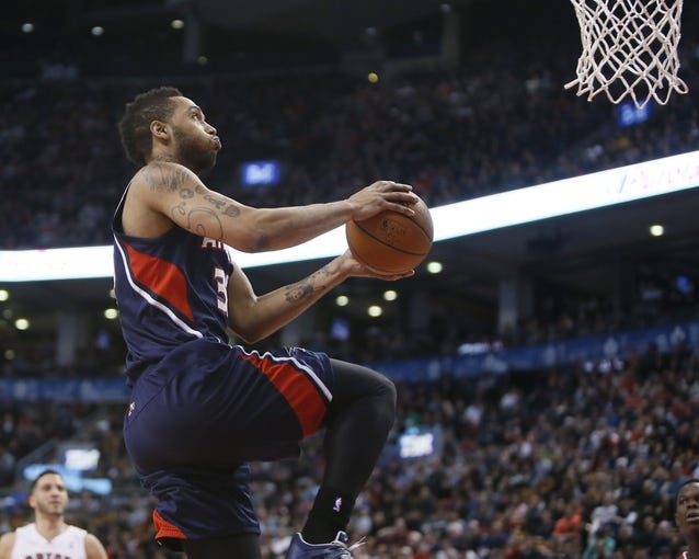 Mar 23, 2014; Toronto, Ontario, CAN; Atlanta Hawks forward Mike Scott (32) goes up to make a basket against the Toronto Raptors during the second half at the Air Canada Centre. Toronto defeated Atlanta 96-86. Mandatory Credit: John E. Sokolowski-USA TODAY Sports