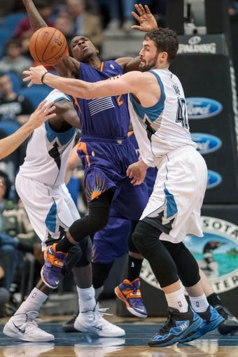 Mar 23, 2014; Minneapolis, MN, USA; Minnesota Timberwolves forward Kevin Love (42) fouls Phoenix Suns guard Eric Bledsoe (2) in the third quarter at Target Center. Phoenix wins 127-120. Mandatory Credit: Brad Rempel-USA TODAY Sports
