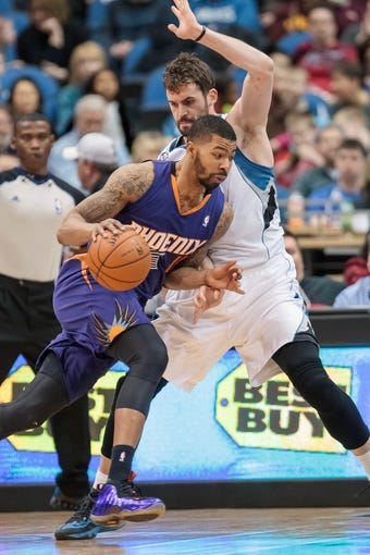 Mar 23, 2014; Minneapolis, MN, USA; Phoenix Suns forward Markieff Morris (11) dribbles in the third quarter against the Minnesota Timberwolves forward Kevin Love (42) at Target Center. Phoenix wins 127-120. Mandatory Credit: Brad Rempel-USA TODAY Sports