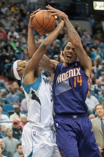 Mar 23, 2014; Minneapolis, MN, USA; Minnesota Timberwolves forward Corey Brewer (13) fouls Phoenix Suns guard Gerald Green (14) in the fourth quarter at Target Center. Phoenix wins 127-120. Mandatory Credit: Brad Rempel-USA TODAY Sports
