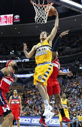 Mar 23, 2014; Denver, CO, USA; Denver Nuggets shooting guard Evan Fournier (94) shoots the ball as Washington Wizards power forward Drew Gooden (90) and shooting guard Bradley Beal (3) defend in the fourth quarter at the Pepsi Center. The Nuggets won 105-102. Mandatory Credit: Isaiah J. Downing-USA TODAY Sports