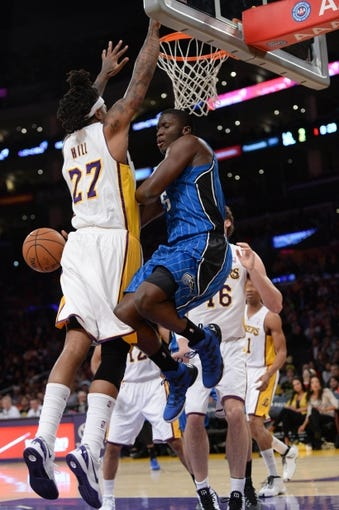 Mar 23, 2014; Los Angeles, CA, USA; Orlando Magic guard Victor Oladipo (5) passes the ball around Los Angeles Lakers forward Jordan Hill (27) at Staples Center. Mandatory Credit: Kirby Lee-USA TODAY Sports