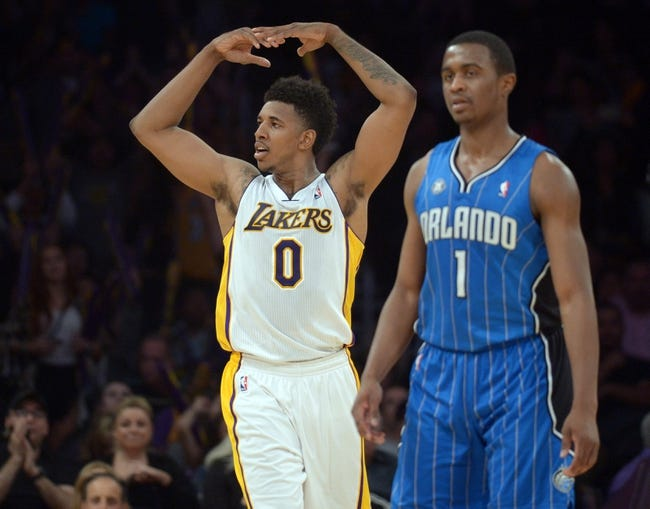 Mar 23, 2014; Los Angeles, CA, USA; Los Angeles Lakers guard Nick Young (0) celebrates in front of Orlando Magic guard Doron Lamb (1) after their game at Staples Center. The Lakers won 103-94. Mandatory Credit: Kirby Lee-USA TODAY Sports