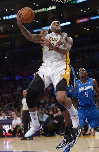 Mar 23, 2014; Los Angeles, CA, USA; Los Angeles Lakers forward Jordan Hill (27) is fouled by Orlando Magic enter Dewayne Dedmon (3) at Staples Center. The Lakers won 103-94. Mandatory Credit: Kirby Lee-USA TODAY Sports