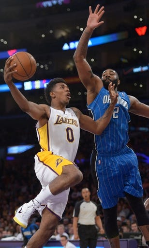 Mar 23, 2014; Los Angeles, CA, USA; Los Angeles Lakers guard Nick Young (0) shoots the ball in front of Orlando Magic forward Kyle O'Quinn (2) at Staples Center. The Lakers won 103-94. Mandatory Credit: Kirby Lee-USA TODAY Sports