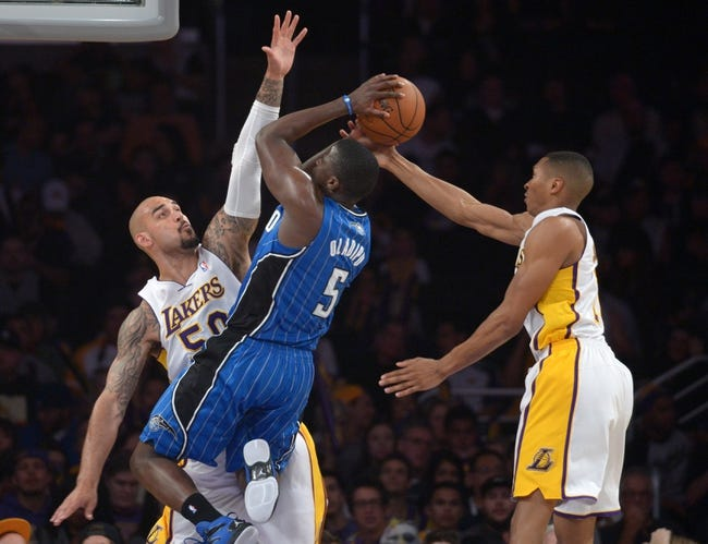 Mar 23, 2014; Los Angeles, CA, USA; Orlando Magic guard Victor Oladipo (5) shoots the ball as Los Angeles Lakers center Robert Sacre (50) and forward Wesley Johnson (11) defend at Staples Center. The Lakers won 103-94. Mandatory Credit: Kirby Lee-USA TODAY Sports