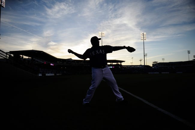 Mar 18, 2014; Surprise, AZ, USA; Texas Rangers first base coach Bengie Molina (4) warms up before facing the Chicago Cubs at Surprise Stadium. Mandatory Credit: Joe Camporeale-USA TODAY Sports