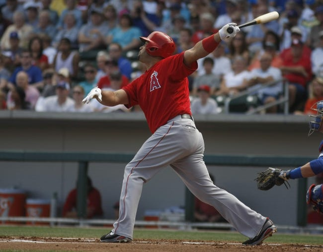 Mar 25, 2014; Mesa, AZ, USA; Los Angeles Angels first baseman Albert Pujols (5) hits an RBI sacrifice fly out against the Chicago Cubs in the first inning at HoHoKam Park. Mandatory Credit: Rick Scuteri-USA TODAY Sports