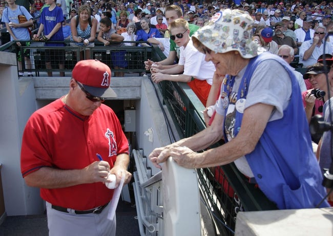 Mar 25, 2014; Mesa, AZ, USA; Los Angeles Angels manager Mike Scioscia (14) signs an autograph for a Cubs fan before a game against the Chicago Cubs at HoHoKam Park. Mandatory Credit: Rick Scuteri-USA TODAY Sports