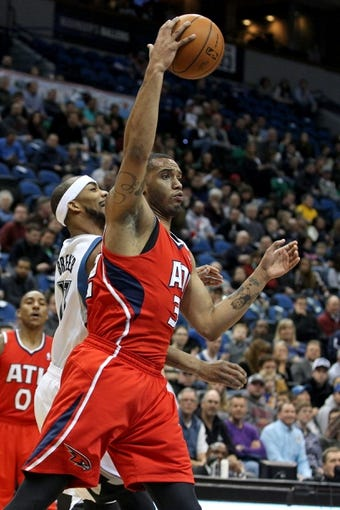 Mar 26, 2014; Minneapolis, MN, USA; Atlanta Hawks forward Mike Scott (32) grabs a rebound over Minnesota Timberwolves forward Corey Brewer (13) during the first quarter at Target Center. Mandatory Credit: Brace Hemmelgarn-USA TODAY Sports