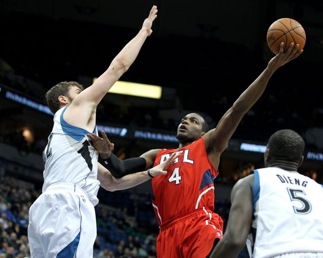 Mar 26, 2014; Minneapolis, MN, USA; Atlanta Hawks forward Paul Millsap (4) shoots over Minnesota Timberwolves forward Kevin Love (42) during the first quarter at Target Center. Mandatory Credit: Brace Hemmelgarn-USA TODAY Sports