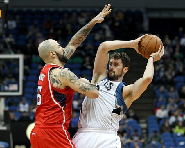 Mar 26, 2014; Minneapolis, MN, USA; Minnesota Timberwolves forward Kevin Love (42) passes around Atlanta Hawks center Pero Antic (6) during the third quarter at Target Center. The Timberwolves defeated the Hawks 107-83. Mandatory Credit: Brace Hemmelgarn-USA TODAY Sports