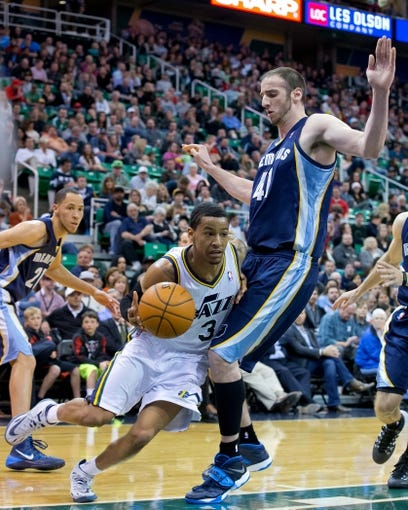 Mar 26, 2014; Salt Lake City, UT, USA; Utah Jazz guard Trey Burke (3) dribbles around Memphis Grizzlies center Kosta Koufos (41) during the second half at EnergySolutions Arena. The Grizzlies won 91-87. Mandatory Credit: Russ Isabella-USA TODAY Sports