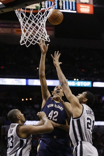 Mar 29, 2014; San Antonio, TX, USA; New Orleans Pelicans center Alexis Ajinca (42) shoots as San Antonio Spurs forward Boris Diaw (33) and San Antonio Spurs forward Tim Duncan (21) defend during the first half at AT&T Center. Mandatory Credit: Soobum Im-USA TODAY Sports
