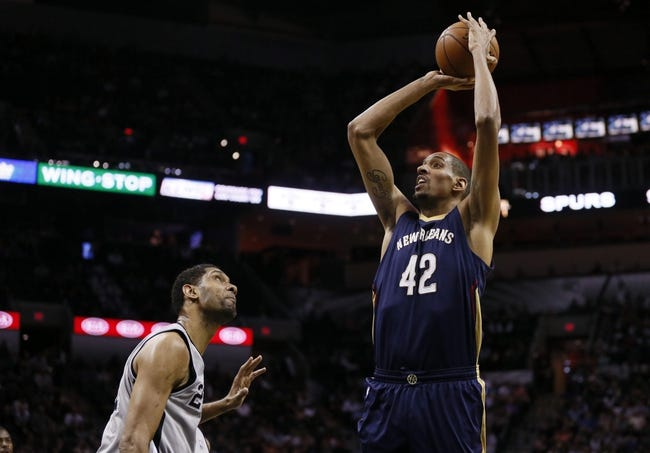 Mar 29, 2014; San Antonio, TX, USA; New Orleans Pelicans center Alexis Ajinca (42) shoots the ball over San Antonio Spurs forward Tim Duncan (left) during the first half at AT&T Center. Mandatory Credit: Soobum Im-USA TODAY Sports