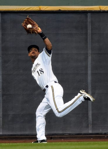 Mar 31, 2014; Milwaukee, WI, USA;   Milwaukee Brewers left fielder Khris Davis (18) makes a running catch of fly ball hit by Atlanta Braves second baseman Dan Uggla (not pictured) in the fourth inning of an opening day baseball game at Miller Park. Mandatory Credit: Benny Sieu-USA TODAY Sports