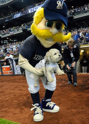 Mar 31, 2014; Milwaukee, WI, USA;  Bernie Brewer carries Hank the Brewer dog during before game against the Atlanta Braves of an opening day baseball game at Miller Park. The Milwaukee Brewers adopted the dog during spring training.  Mandatory Credit: Benny Sieu-USA TODAY Sports