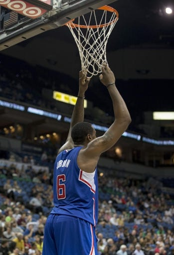 Mar 31, 2014; Minneapolis, MN, USA; Los Angeles Clippers center DeAndre Jordan (6) hangs the net during a free throw in the second half against the Minnesota Timberwolves at Target Center. The Clippers won 114-104. Mandatory Credit: Jesse Johnson-USA TODAY Sports