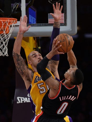 Apr 1, 2014; Los Angeles, CA, USA;  Los Angeles Lakers center Robert Sacre (50) blocks a shot by Portland Trail Blazers guard Damian Lillard (0) during the second half of the game at Staples Center. Trail Blazers won 124-112. Mandatory Credit: Jayne Kamin-Oncea-USA TODAY Sports
