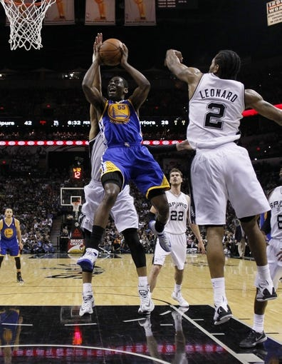 Apr 2, 2014; San Antonio, TX, USA; Golden State Warriors guard Jordan Crawford (55) shoots while being defended by San Antonio Spurs forward Tim Duncan (behind) and Kawhi Leonard (2) during the first half at AT&T Center. Mandatory Credit: Soobum Im-USA TODAY Sports