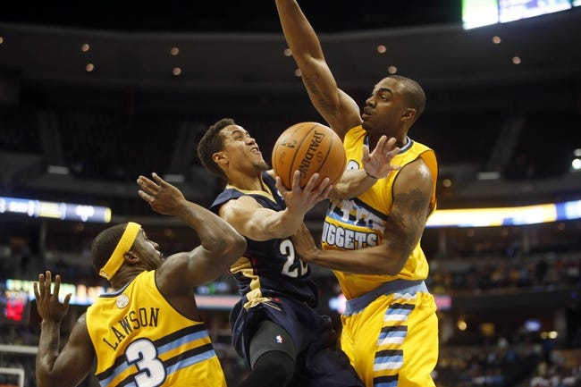 Apr 2, 2014; Denver, CO, USA; New Orleans Pelicans guard Brian Roberts (middle) drives to the basket between Denver Nuggets guard Ty Lawson (3) and forward Darrell Arthur (00) during the first half at Pepsi Center. Mandatory Credit: Chris Humphreys-USA TODAY Sports