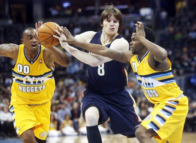 Apr 2, 2014; Denver, CO, USA; New Orleans Pelicans forward Luke Babbitt (8) drives to the basket between Denver Nuggets guard Aaron Brooks (0) and forward Darrell Arthur (00) during the first half at Pepsi Center. Mandatory Credit: Chris Humphreys-USA TODAY Sports