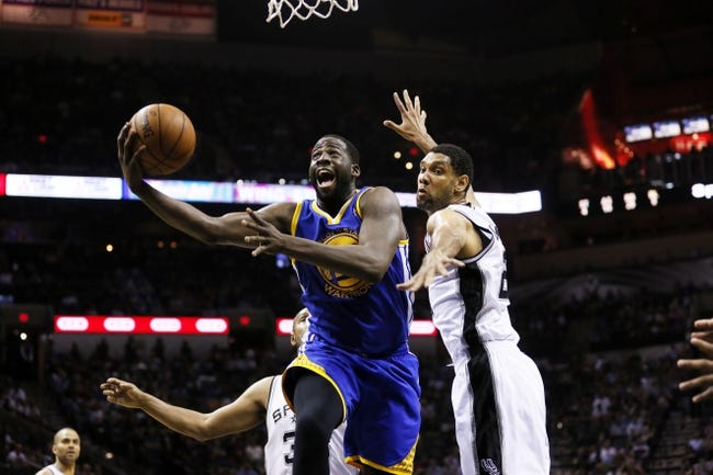 Apr 2, 2014; San Antonio, TX, USA; Golden State Warriors forward Draymond Green (left) shoots the ball past San Antonio Spurs forward Tim Duncan (right) during the second half at AT&T Center. The Spurs won 111-90. Mandatory Credit: Soobum Im-USA TODAY Sports