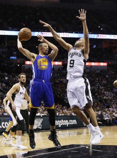 Apr 2, 2014; San Antonio, TX, USA; Golden State Warriors guard Stephen Curry (30) looks to pass the ball as San Antonio Spurs guard Tony Parker (9) defends during the second half at AT&T Center. The Spurs won 111-90. Mandatory Credit: Soobum Im-USA TODAY Sports