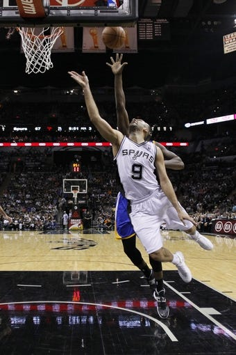 Apr 2, 2014; San Antonio, TX, USA; San Antonio Spurs guard Tony Parker (9) shoots the ball past Golden State Warriors forward Draymond Green (behind) during the second half at AT&T Center. The Spurs won 111-90. Mandatory Credit: Soobum Im-USA TODAY Sports
