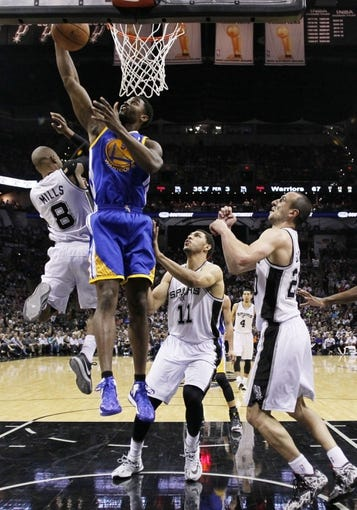 Apr 2, 2014; San Antonio, TX, USA; Golden State Warriors forward Marreese Speights (5) pulls down a rebound over San Antonio Spurs guard Patrick Mills (8) during the second half at AT&T Center. The Spurs won 111-90. Mandatory Credit: Soobum Im-USA TODAY Sports