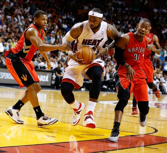 Mar 31, 2014; Miami, FL, USA; Miami Heat forward LeBron James (6) drives to the basket between Toronto Raptors guard Kyle Lowry (left) and forward Terrence Ross (31) in the second half of a game against the Toronto Raptors at American Airlines Arena. Mandatory Credit: Robert Mayer-USA TODAY Sports