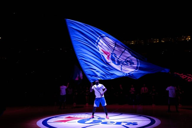 Apr 2, 2014; Philadelphia, PA, USA; A member of the Philadelphia 76ers flight squad waves a 76ers flag prior to the start of the game against the Charlotte Bobcats at the Wells Fargo Center. The Bobcats defeated the Sixers 123-93. Mandatory Credit: Howard Smith-USA TODAY Sports