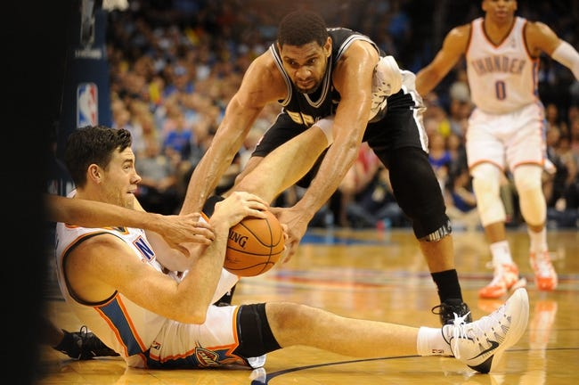 Apr 3, 2014; Oklahoma City, OK, USA; Oklahoma City Thunder forward Nick Collison (4) fights for a loose ball with San Antonio Spurs forward Tim Duncan (21) during the third quarter at Chesapeake Energy Arena. Mandatory Credit: Mark D. Smith-USA TODAY Sports