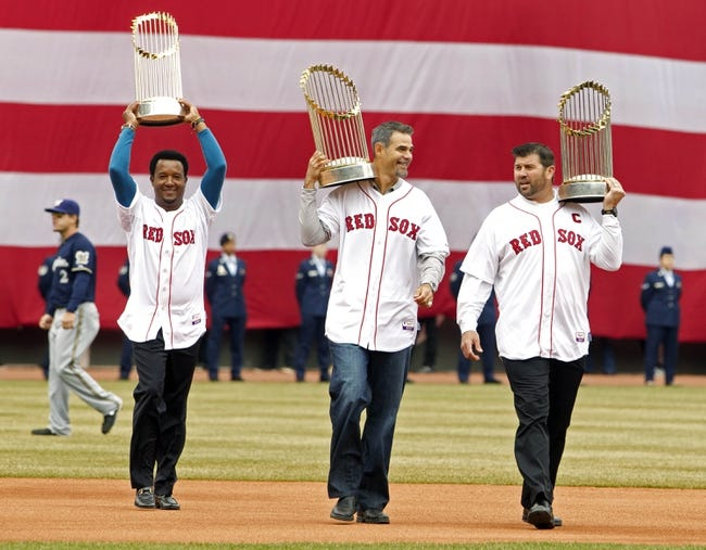Apr 4, 2014; Boston, MA, USA; Boston Red Sox former players Pedro Martinez , Mike Lowell and Jason Varitek carry out World Series trophies during pre-game ceremonies before the game against the Milwaukee Brewers at Fenway Park. Mandatory Credit: David Butler II-USA TODAY Sports