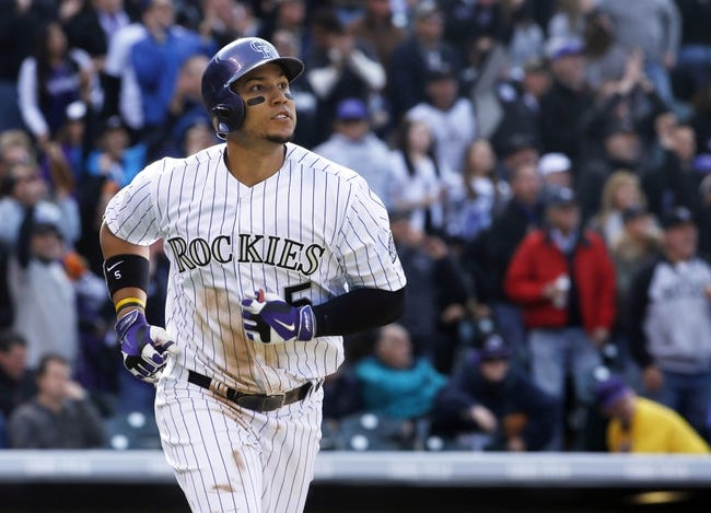 Apr 4, 2014; Denver, CO, USA; Colorado Rockies left fielder runs the bases after hitting a home run during the sixth inning against the Arizona Diamondbacks at Coors Field. Mandatory Credit: Chris Humphreys-USA TODAY Sports