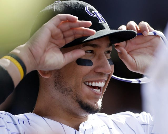 Apr 4, 2014; Denver, CO, USA; Colorado Rockies left fielder Carlos Gonzalez (5) in the dugout during the sixth inning against the Arizona Diamondbacks at Coors Field. Mandatory Credit: Chris Humphreys-USA TODAY Sports