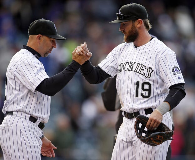 Apr 4, 2014; Denver, CO, USA; Colorado Rockies left fielder Charlie Blackmon (19) is congratulated by manager Walt Weiss (left) after the game against the Arizona Diamondbacks at Coors Field. Blackmon went six for six during the game, tying a franchise record. The Rockies won 12-2. Mandatory Credit: Chris Humphreys-USA TODAY Sports