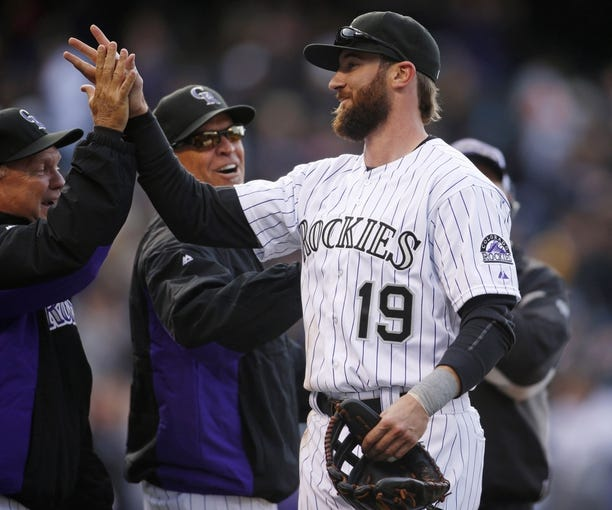 Apr 4, 2014; Denver, CO, USA; Colorado Rockies left fielder Charlie Blackmon (19) is congratulated by teammates after the game against the Arizona Diamondbacks at Coors Field. Blackmon went six for six during the game, tying a franchise record. The Rockies won 12-2. Mandatory Credit: Chris Humphreys-USA TODAY Sports