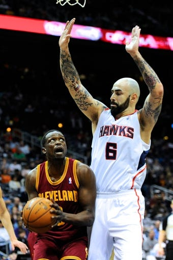 Apr 4, 2014; Atlanta, GA, USA; Cleveland Cavaliers forward Luol Deng (9) is defended by Atlanta Hawks center Pero Antic (6) during the first half at Philips Arena. Mandatory Credit: Dale Zanine-USA TODAY Sports