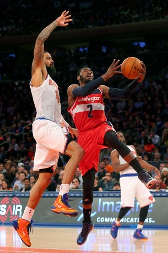 Apr 4, 2014; New York, NY, USA; Washington Wizards point guard John Wall (2) drives to the basket past New York Knicks center Tyson Chandler (6) during the second quarter of a game at Madison Square Garden. Mandatory Credit: Brad Penner-USA TODAY Sports