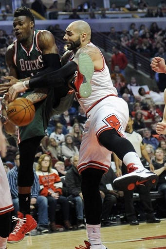 Apr 4, 2014; Chicago, IL, USA; Milwaukee Bucks forward Jeff Adrien (12) is defended by Chicago Bulls forward Carlos Boozer (5) during the first quarter at the United Center. Mandatory Credit: David Banks-USA TODAY Sports