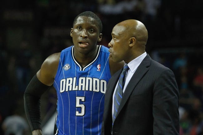 Apr 4, 2014; Charlotte, NC, USA; Orlando Magic guard Victor Oladipo (5) talks with head coach Jacque Vaughn during the second half against the Charlotte Bobcats at Time Warner Cable Arena. The Bobcats defeated the Magic 91-80. Mandatory Credit: Jeremy Brevard-USA TODAY Sports