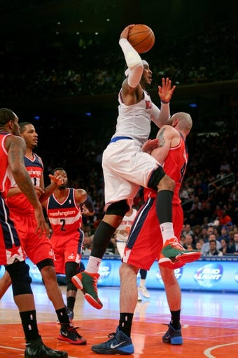 Apr 4, 2014; New York, NY, USA; New York Knicks small forward Carmelo Anthony (7) commits an offensive foul as he drives on Washington Wizards center Marcin Gortat (4) during the third quarter of a game at Madison Square Garden. The Wizards defeated the Knicks 90-89. Mandatory Credit: Brad Penner-USA TODAY Sports