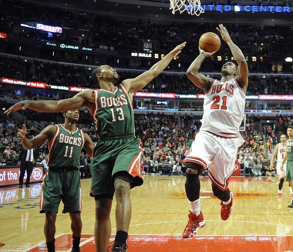 Apr 4, 2014; Chicago, IL, USA;  Chicago Bulls guard Jimmy Butler (21) is defended by Milwaukee Bucks guard Ramon Sessions (13) during the second half at the United Center. The Chicago Bulls defeated the Milwaukee Bucks 102-90. Mandatory Credit: David Banks-USA TODAY Sports