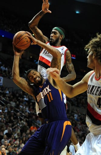 Apr 4, 2014; Portland, OR, USA; Phoenix Suns forward Markieff Morris (11) is fouled by Portland Trail Blazers guard Will Barton (5) during the first quarter of the game at Moda Center. Mandatory Credit: Steve Dykes-USA TODAY Sports