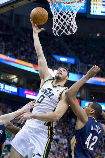 Apr 4, 2014; Salt Lake City, UT, USA; Utah Jazz center Enes Kanter (0) shoots shoots over New Orleans Pelicans center Alexis Ajinca (42) during the second half at EnergySolutions Arena. The Jazz won 100-96. Mandatory Credit: Russ Isabella-USA TODAY Sports